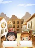 Due bambini vicino alle barre di salone che tengono due insegne vuote Fotografie Stock Libere da Diritti