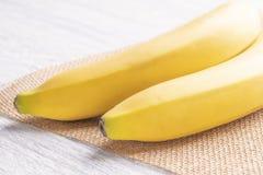 Due banane mature su un tovagliolo di vimini al sole immagini stock