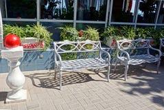 Due banchi grigi del metallo sul marciapiede contro la parete con le finestre ed i vasi da fiori con le piante ed i fiori fotografie stock libere da diritti