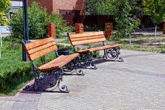 Due banchi marroni e un'urna sul marciapiede nel parco Fotografia Stock