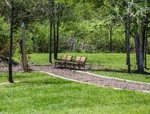 Due banchi vuoti lungo il percorso del parco Fotografia Stock
