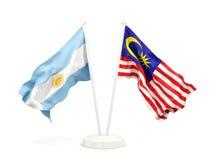 Due bandiere d'ondeggiamento dell'Argentina e della Malesia isolate su bianco illustrazione di stock