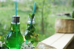 Due barattoli con i tubi sotto forma di lampadine hanno riempito di supporto di limonata su un banco in natura, vicino ai fiori d Immagini Stock