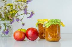 Due barattoli dell'inceppamento e delle mele di Apple sulla tavola bianca Fotografia Stock