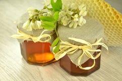 Due barattoli di miele delizioso fresco con i fiori dell'acacia e del favo Fotografia Stock