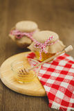 Due barattoli di miele e dei favi isolati su bianco Immagini Stock