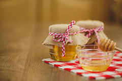 Due barattoli di miele e dei favi isolati su bianco Fotografia Stock