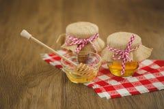 Due barattoli di miele e dei favi isolati su bianco Fotografia Stock Libera da Diritti