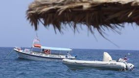 Due barche attraccate guidano le onde vicino alla spiaggia di Kamari, Santorini, Grecia archivi video