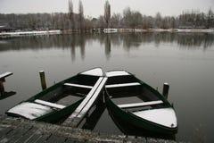 Due barche di rematura coperte di neve nel lago di inverno Immagine Stock Libera da Diritti
