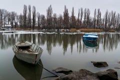 Due barche sul fiume su una mattina di inverno con la riflessione nell'acqua immagini stock libere da diritti