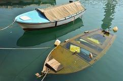 Due barche sull'ancoraggio, uno sta affondando fotografia stock