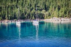 Due barche a vela ancorate in una baia verde smeraldo fotografia stock
