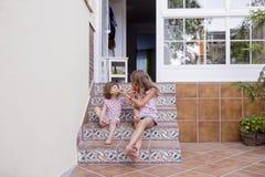 Due bei bambini della sorella che mangiano anguria a casa sulle scale Amore della famiglia ed aria aperta di stile di vita fotografia stock