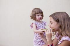 Due bei bambini della sorella che mangiano anguria a casa sulle scale Amore della famiglia ed aria aperta di stile di vita fotografie stock