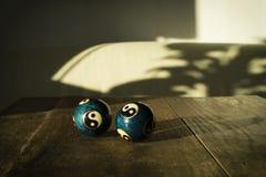 Due bei baodingballs di yang e del yin sulla tavola di legno scura in sole fotografia stock
