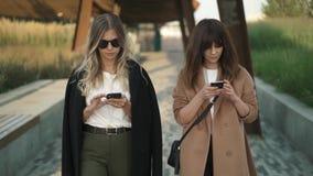 Due bei blogger di modo che camminano nel parco e web che pratica il surfing sugli smartphones video d archivio