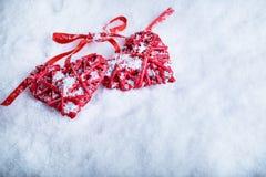 Due bei cuori rossi d'annata romantici insieme su un fondo bianco di inverno della neve Amore e concetto di giorno di biglietti d Fotografie Stock