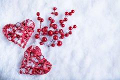 Due bei cuori rossi d'annata romantici insieme sul fondo bianco di inverno della neve Amore e concetto di giorno di biglietti di  Immagine Stock