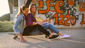 Due bei e giovani donne divertendosi con il pattino video d archivio