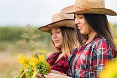 Due bei e giovani ragazze dell'agricoltore che esaminano il raccolto del girasole Fotografia Stock Libera da Diritti