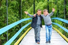 Due bei piccoli tipi che corrono lungo il ponte nei Carpathians fotografia stock