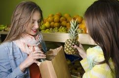 Due bei, ragazze di sguardo naturali che comprano frutta fotografia stock libera da diritti