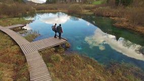 Due bei viaggiatori con zaino e sacco a pelo che esaminano il bello lago stock footage