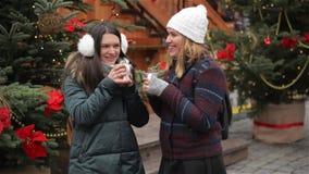 Due belle amiche che parlano e che ridono sul mercato di Natale Amici che bevono bevanda calda e che si divertono sul video d archivio