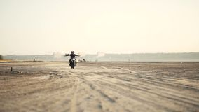 Due belle amiche guidano senza mani su un motociclo sul deserto al tramonto Motociclista femminile Movimento lento archivi video