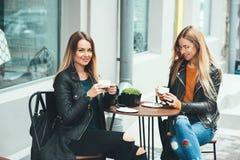 Due belle donne alla moda attraenti sono sedersi all'aperto nel coffe bevente del caffè e tè che parlano e che godono di grande g Fotografie Stock