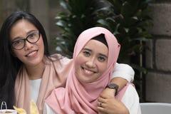Due belle donne asiatiche che esaminano macchina fotografica mentre abbracciando ciascuno immagini stock libere da diritti