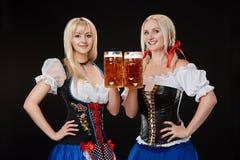 Due belle donne bionde stanno tenendo i vetri della birra in mani e stanno su fondo nero in studio Immagine Stock