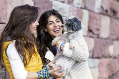 Due belle donne che abbracciano il loro piccolo cane all'aperto Immagine Stock