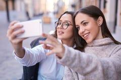 Due belle donne che fanno selfie dal telefono nella parte centrale della città fotografie stock libere da diritti