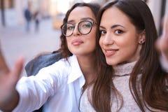 Due belle donne che fanno selfie dal telefono nella parte centrale della città fotografia stock