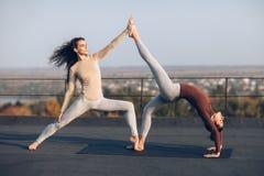 Due belle donne che fanno virabhadrasana di asana di yoga sul tetto Immagini Stock Libere da Diritti