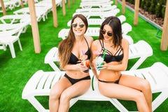 Due belle donne che hanno cocktail insieme dalla piscina Estate fotografia stock libera da diritti