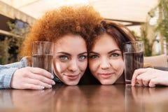 Due belle donne che tengono i bicchieri d'acqua che si siedono in caffè Fotografie Stock Libere da Diritti