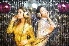Due belle donne sexy della discoteca in danci dei catsuits dell'argento e dell'oro Immagine Stock