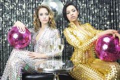 Due belle donne sexy della discoteca in danci dei catsuits dell'argento e dell'oro Fotografie Stock Libere da Diritti