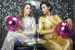 Due belle donne sexy della discoteca in danci dei catsuits dell'argento e dell'oro Fotografia Stock