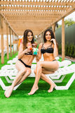 Due belle donne sexy nel bere del bikini cocktail mentre rilassandosi nella piscina Vacanze estive, viaggio, raggiro di vacanza Fotografie Stock