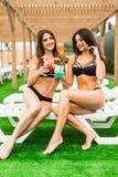 Due belle donne sexy nel bere del bikini cocktail mentre rilassandosi nella piscina Vacanze estive, viaggio, raggiro di vacanza Fotografie Stock Libere da Diritti