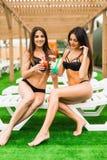 Due belle donne sexy nel bere del bikini cocktail mentre rilassandosi nella piscina Vacanze estive, viaggio, raggiro di vacanza Immagini Stock Libere da Diritti