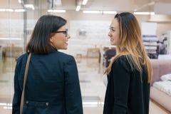 Due belle donne sorridenti adulte nel profilo, femmine di conversazione primo piano, fondo all'interno immagini stock libere da diritti