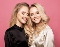 Due belle giovani donne in abbigliamento casual che posa sopra il fondo rosa fotografie stock