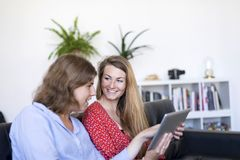 Due belle giovani donne a casa che si siedono sul sofà mentre usando un computer e sorridere del PC della compressa immagine stock