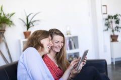 Due belle giovani donne a casa che si siedono sul sofà mentre usando un computer e sorridere del PC della compressa fotografia stock