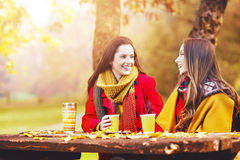 Due belle giovani donne che parlano e che godono un giorno di autunno immagine stock
